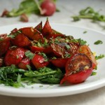 plate of roasted radishes with butter and herbs on tablecloth