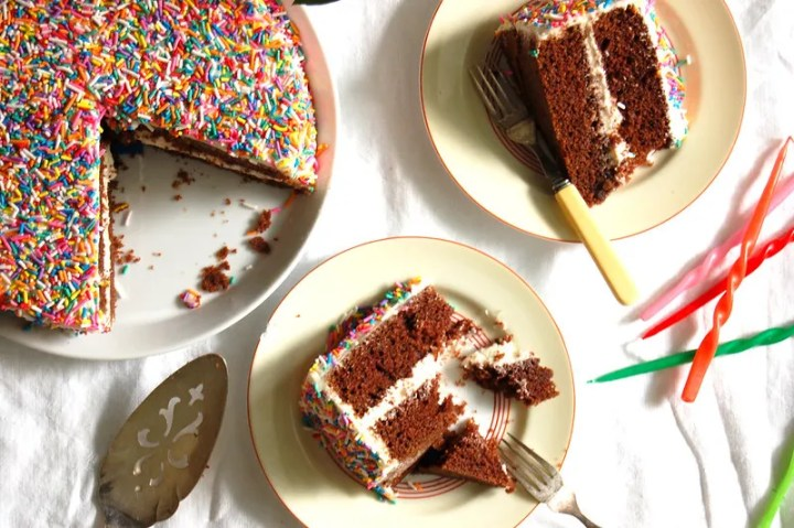 not-red velvet layer cake slices on plates with sprinkles birthday party spread