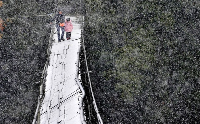Crossing a broken bridge in the snow to get to school in Dujiangyan, Sichuan Province, China