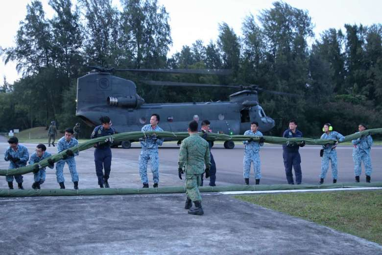The State Flag Team carrying the rolled up State Flag into the CH-47D Chinook helicopter. (via TheRSAF)