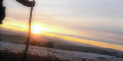 Chico joven con un palo observando una puesta de sol en una montaña nevada