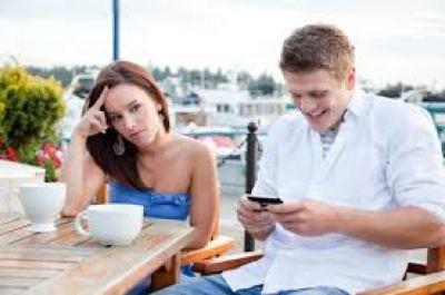 Un chico entretenido con su móvil mientras su novia espera algo de atención