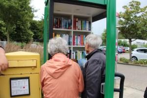Foto Telefonzelle mit Büchern und ersten Nutzern