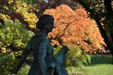 Orange leuchtender Ahorn mit einer scharzen Statue im Vordergrund.