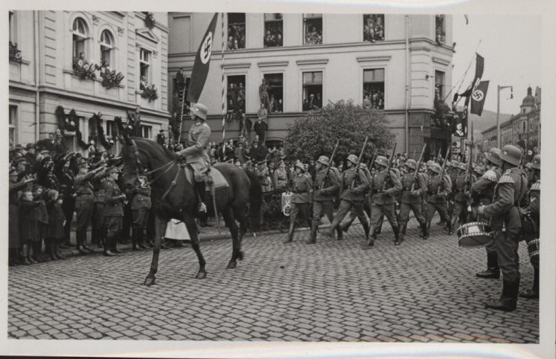Parade von Wehrmachtssoldaten mit Offizieren zu Pferd am Ende der Bahnhofstraße im Bereich Hotel Monopol mit Publikum am Straßenrand in der Siegener Innenstadt.