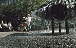Zwei Kinder spielen an einem Brunnen in der Altstadt von Siegen