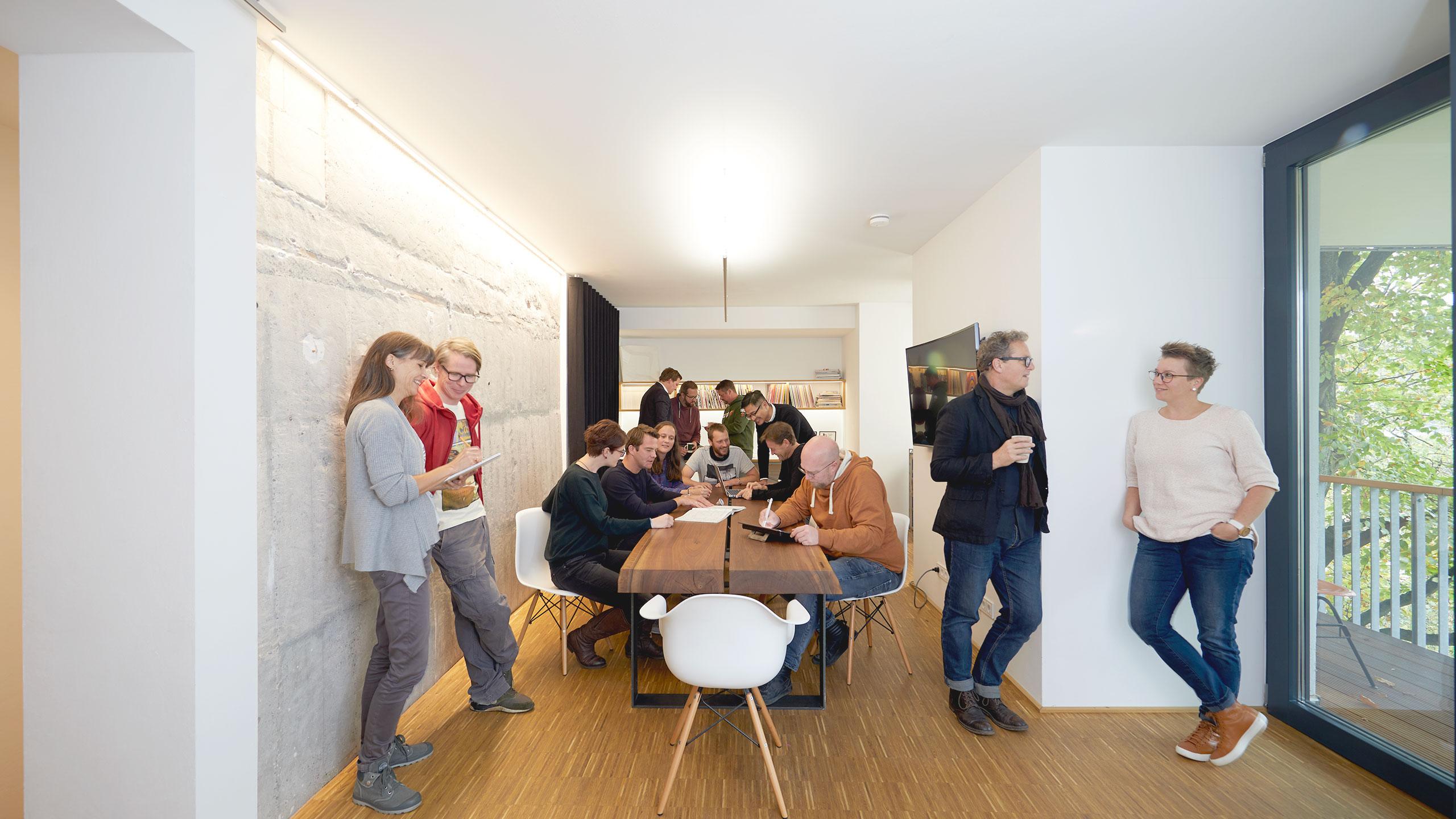14 Frauen und Männer stehen und sitzen in einem Raum im Modulbüro im ehemaligen Bunker in der Oberstadt Siegen.