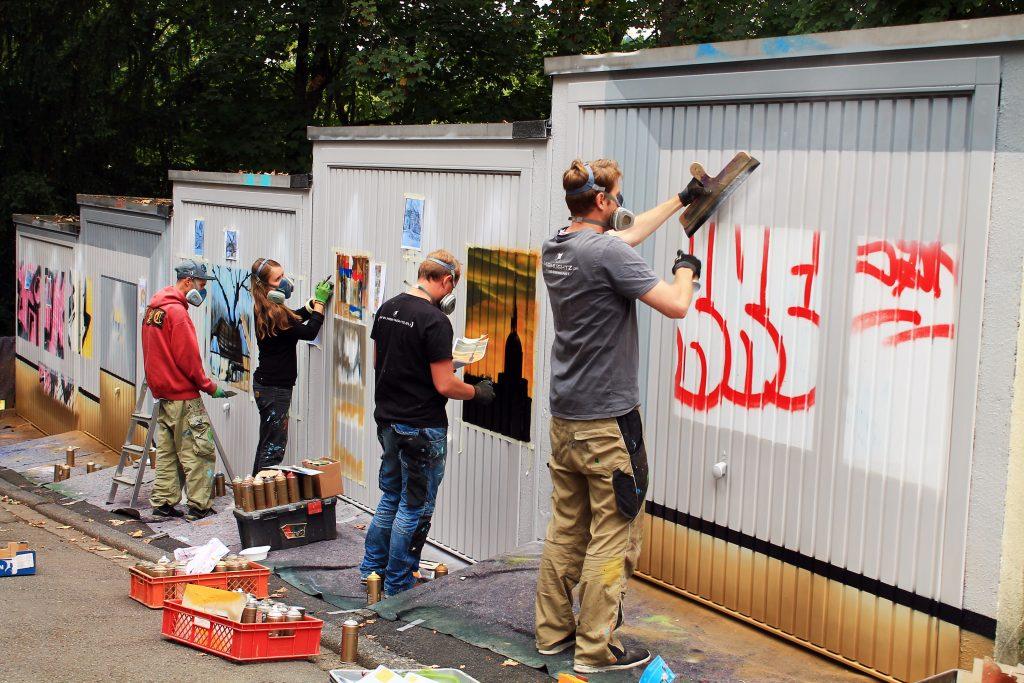 Vier Sprayer von Highlightz bearbeiten Garagentore in der Siegbergstraße in Siegen.