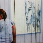 in Beispiel der neugestalteten Garagentore in der Siegbergstraße in Siegen. Motiv: Eine junge Frau betrachtet Bilder an einer Museumswand. Mit freundlicher Genehmigung von Martin Zielke.