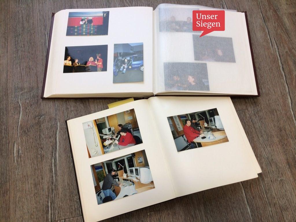 """Zwei geöffnete Fotoalben auf Tisch. Die Produzenten von """"Das Leiden vom Schlossberg"""" im Studio in Siegen."""