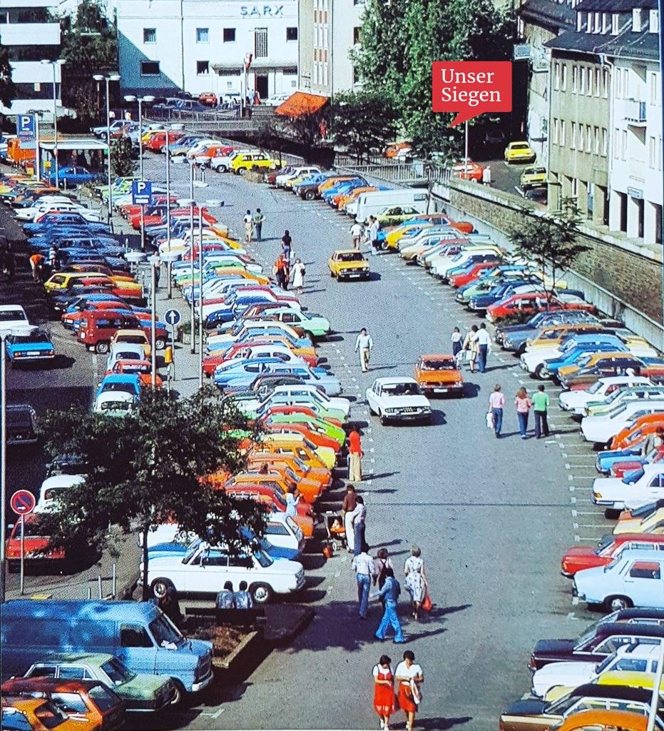 Farbenfrohes Foto aus den 1970er Jahren. Auf der Siegplatte parken viele bunte Autos.