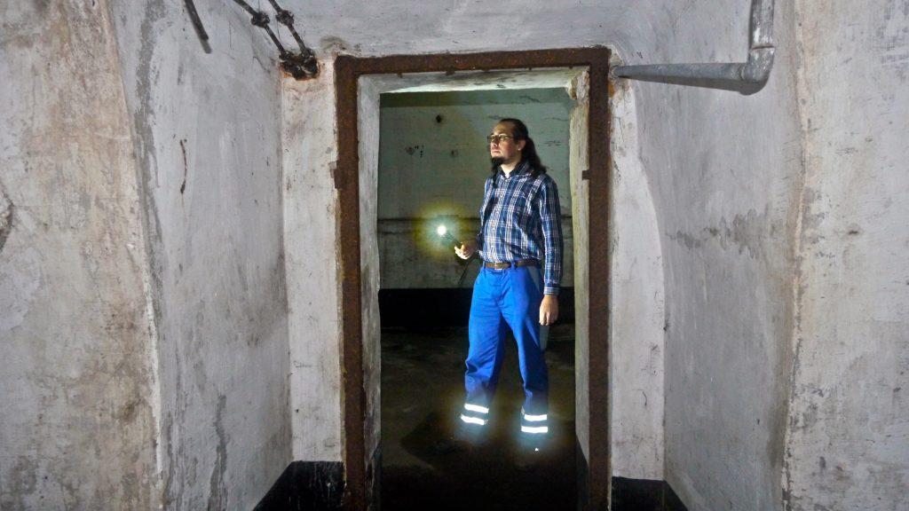 Markus Jung von Siegener Unterwelten mit Taschenlampe in altem Gang.