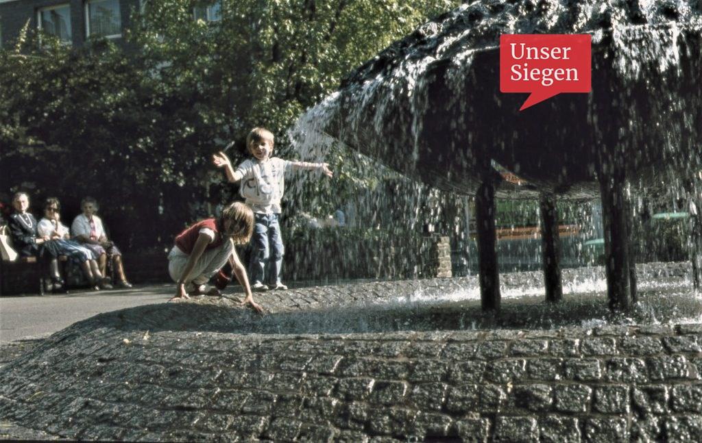 """Zwei Kinder spielen am Brunnen, dem """"Wasserspiel"""" in der Fißmer-Anlage bei Rathaus und Markt in der Oberstadt Siegen. 1980er Jahre."""
