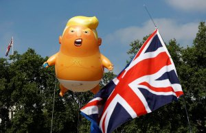 Demonstrators float a blimp portraying U.S. President Donald Trump, next to a Union Flag above Parliament Square, during the visit by Trump and First Lady Melania Trump in London, Britain July 13, 2018. REUTERS/Peter Nicholls