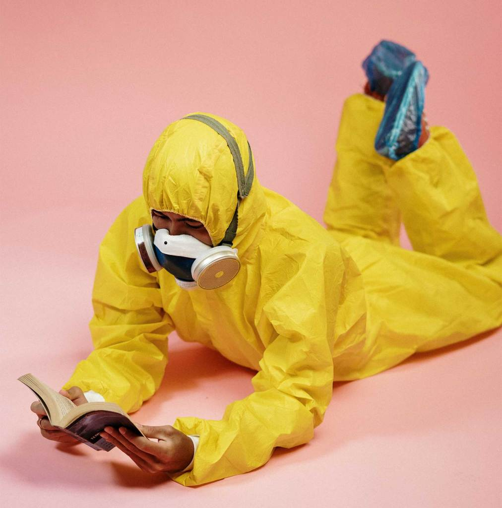 person-in-yellow-coveralls-and-respiratory-mask-reading-a-book