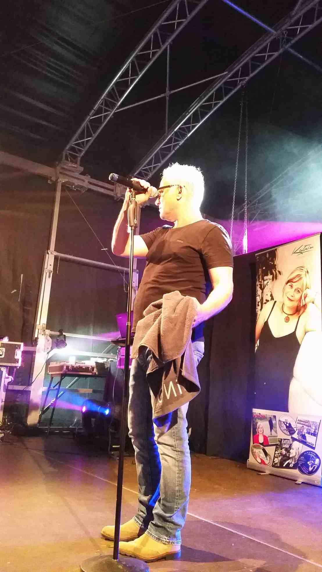 Nino auf der Bühne in der Hand hat er ein graues Handtuch