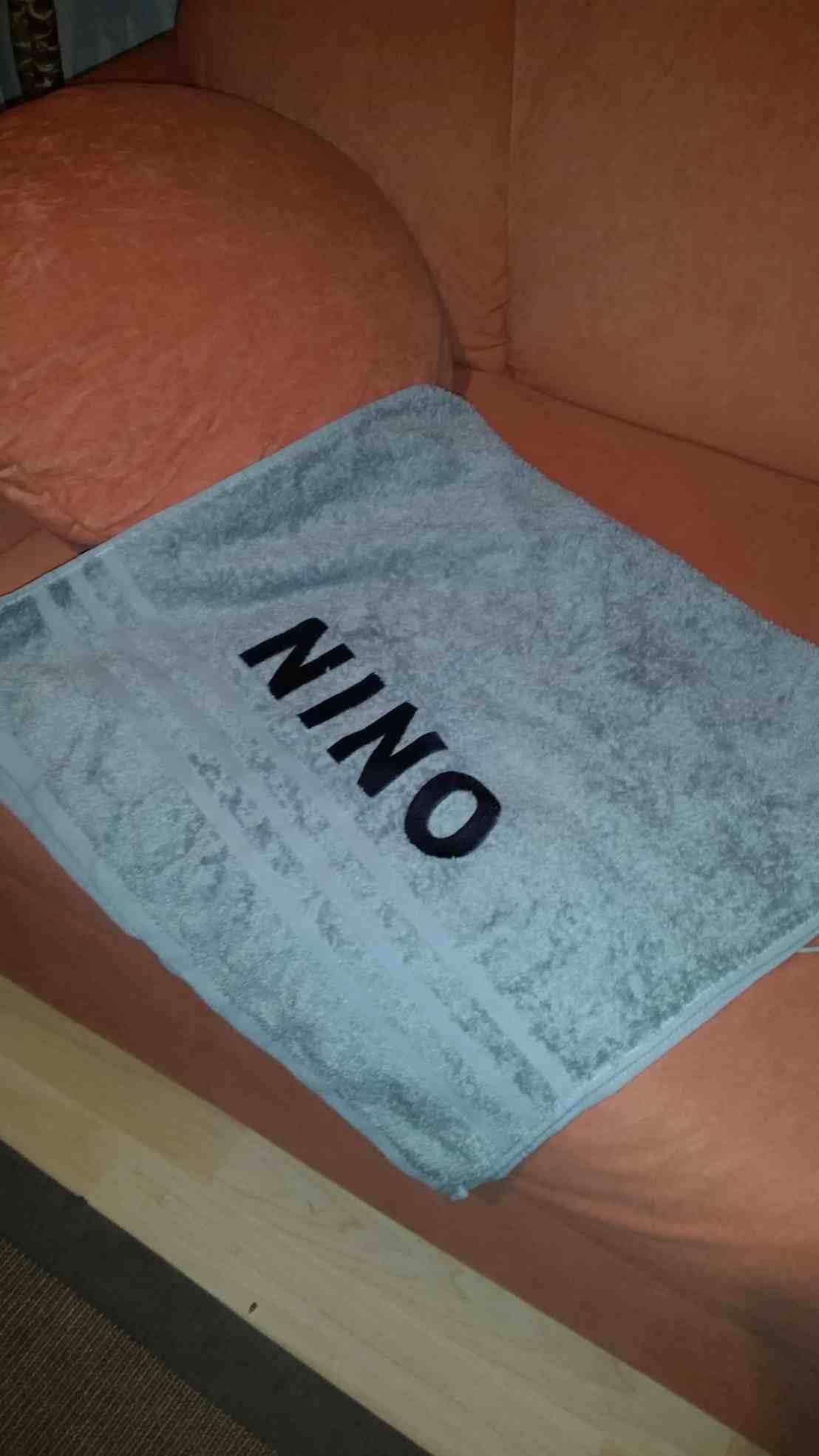 Ein graues Handtuch mit stickerei NINO