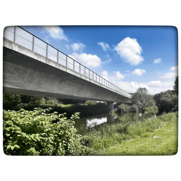 Eine Autobrücke führt über das malerische Flussbett der Wiese