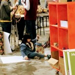 Little girl wrapping a gift at the Family Giving Tree warehouse.