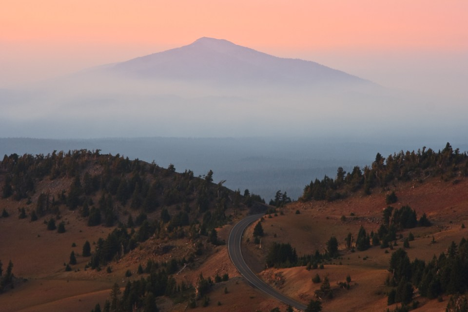 Crater Lake National Park's Rim Drive leads off to a distant mountain shrouded in smoke and haze from a series of forest fires. Photo by Cameron Booth/Flickr