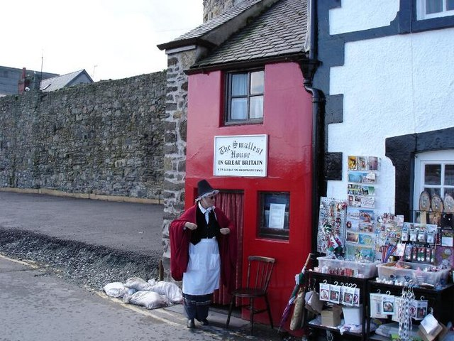 Woman in front of the smallest house in Great Britain