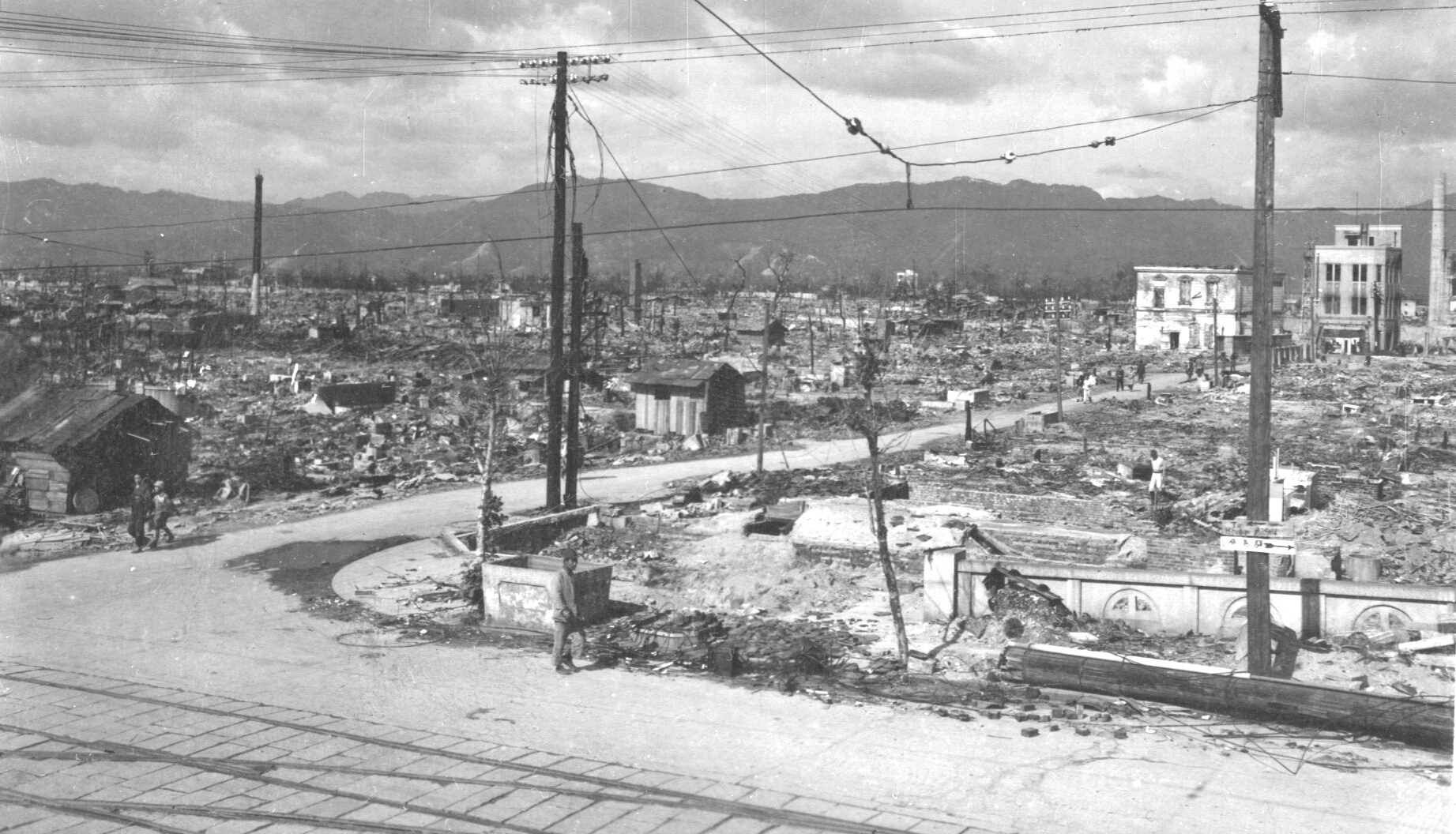 Photograph of Hiroshima after atomic bomb. A road is in teh foreground. Two people are walking in the background. Most of the scene is rubble with a few buildings standing in the background.