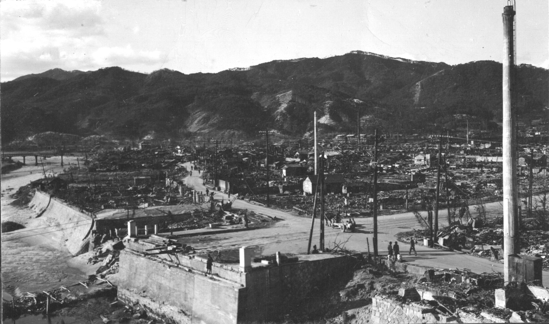 Photograph of Hiroshima after atomic bomb. An intersection of two roads is in the foreground and mountains are in the background.
