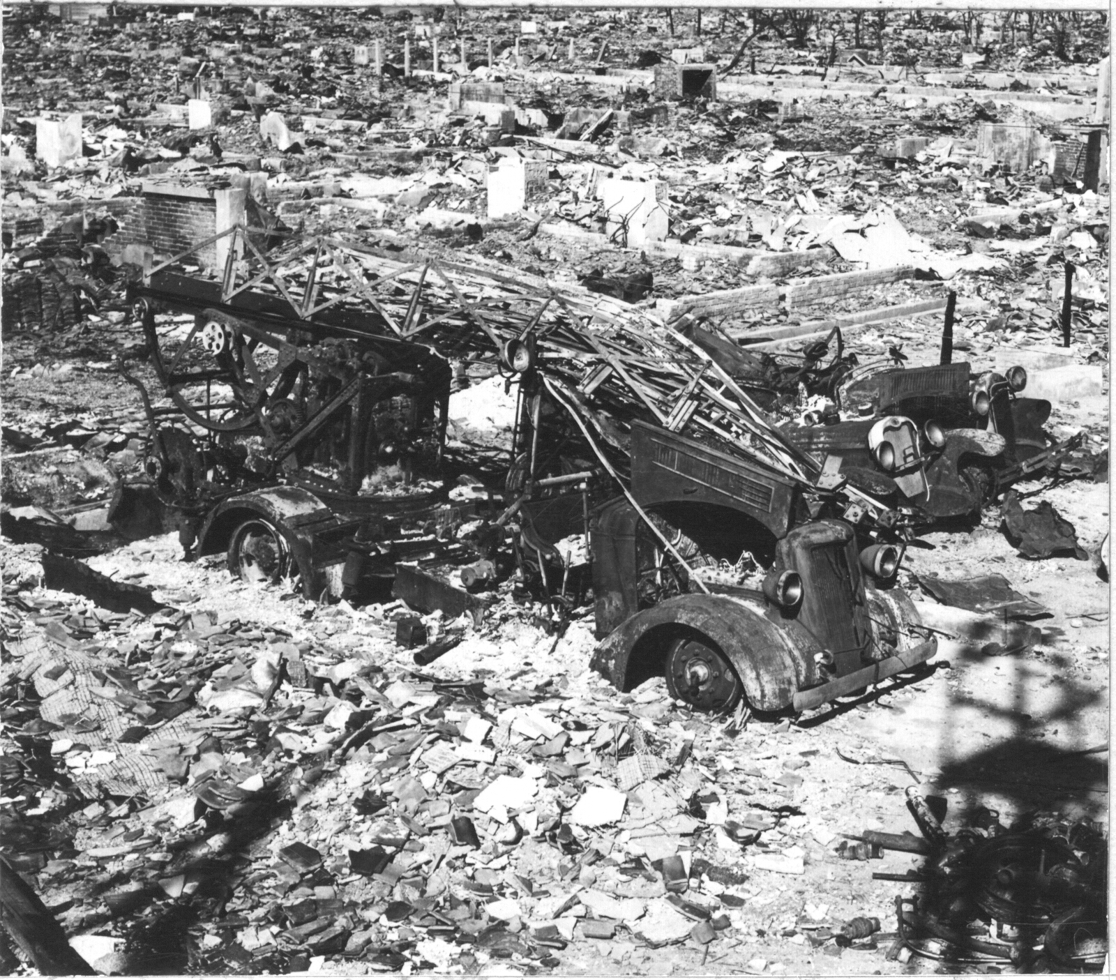 Photograph of Hiroshima after the atomic bomb. A burned out fire engine is surrounded by rubble.