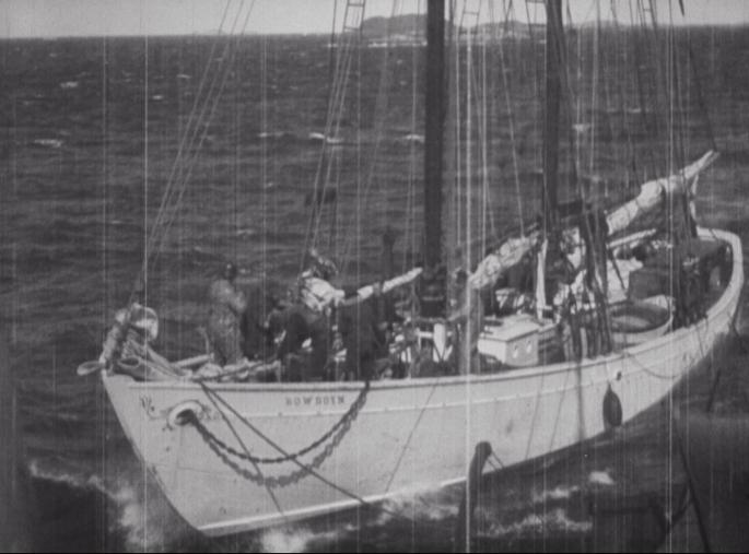"""An image of a white boat. The name reads """"BOWDOIN"""". There are crew members on deck. The sails are not raised."""