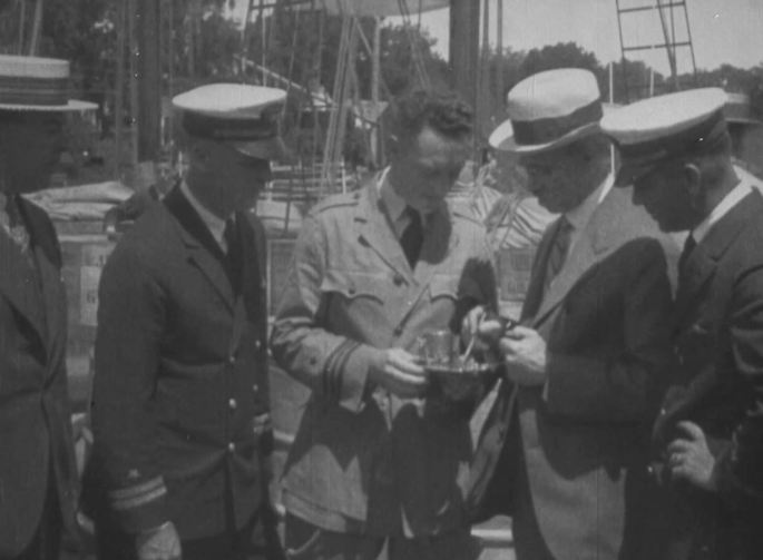 At the launch of the expedition, Byrd (center), shows off an instrument of some sort while pilot Lt. M.A. Schur (left) looks on.