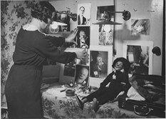 """The famous clown """"Grock"""" back in Berlin. The lady who is decorating his dressing room with photographs is Mrs. Grock. 306-NT-290-MM-2. Source: Wide World Photos (Potential copyright restrictions)."""