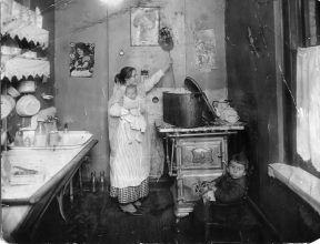 Laundry. Woman holding a baby in one arm and stirring a wash boiler filled with clothes. 3/31/19 (86-G-6U-2)