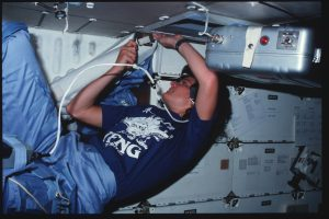 On middeck, Mission Specialist (MS) Ride lifts velcroed insulation and netting from around overhead panels MO42F and MO58F with a screwdriver. DC Utility Power panel MO30F and ceiling-mounted carry-on food warmer appear in view.
