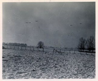 """1111-SC-415373 """"Badly needed medical supplies and ammunition are dropped in a field, while the 101st Airborne Division was besieged by the Germans. It was snowing when this mission was made, making it dangerous for the C-47 pilot."""" Photo taken 12/25/1944"""