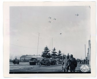 """111-SC-415376 """"Troops of the 101st Airborne Division watch C-47's drop supplies to them."""" Photo taken 12/26/1944"""