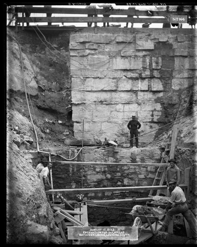 """Men working down in an excavation site, their equipment precariously supported by two by four planks of wood. One man observes the workers from a shelf halfway down the excavation, while the legs of people standing some twenty feet above at the top of the image. Label on the original photograph reads, """"August 17, 1893. Excavation for bulkhead between locks, looking south."""""""