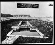"""A fenced off area around an old lock, about the size of a private swimming pool. Label on the photograph reads, """"First Lock at St. Marys Falls. Built 1797-8, for bateaux in Sault Ste. Marie, Ontario by Montreal Fur Co. Destroyed 1814. Floors and foundation uncovered 1889, restored 1890."""""""