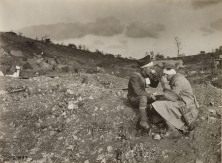 Original Caption: Two wounded soldiers enjoying refreshments from Red Cross outpost station at Chatel Chehery, Argonne Forest, Ardennes, France. October 10, 1918. Local Identifier: 111-SC-29833