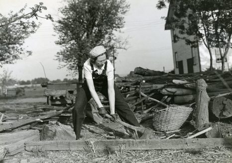 """""""Miss Mildred Saums of Three Bridges, Hunterdon County, NJ, can do as good a job at the family wood pile on her widowed mother's farm as her brother who runs the farm. She helps with the morning and evening chores. Daytimes she works as chief clerk at the Flemington Auction Market cooperative Association."""" Date Taken: May 1942 (Local ID: 16-G-168-N-3983)"""
