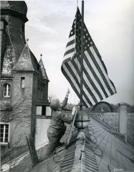 "111-SC-231596 ""1st/Sgt. David G. Lemkowitz...battalion adjutant 505th Parachute Infantry Regiment, 82nd Airborne Division, U.S. 15th Army raises American flag atop 17th century castle somewhere in Germany..."" 04/12/45"