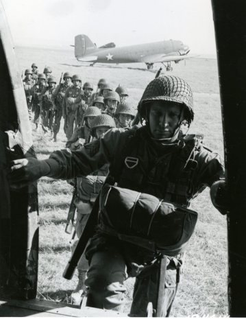 """111-SC-184014 """"Paratroopers of the 82nd Airborne Division entering a plane from which they will leap, during invasion training under direction of 5th Army, commanded by Lt. General Mark W. Clark, Oujd, Fr. Morocco, N. Africa. Also: 505th Infantry."""" June 2nd 1943."""