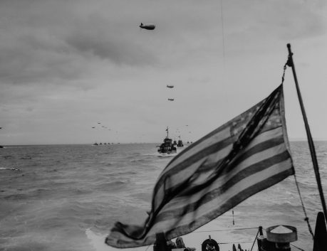 26-G-2399: [ORIGINAL CAPTION:] OLD GLORY MOVES TO NEW GLORY: Columns of Coast Guard LCI's, protected by barrage balloons against low flying Nazi strafers, advance upon the beaches of France in the wake of the Stars and Stripes. A Coast Guard combat photographer, going into the invasion on an LCI, caught this picture of the advance guard of the Liberation Fleet in the English Channel.