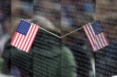 """330-CFD-DF-SD-04-12155: The reflection of a small American Flag placed on the Vietnam Memorial located in Washington, District of Columbia (DC), during the observance of Veterans Day 2002. Every year people from around the world pilgrimage to the Vietnam Memorial known by some as """"The Wall"""" to etch from the wall onto a piece of paper a name of a departed loved one."""