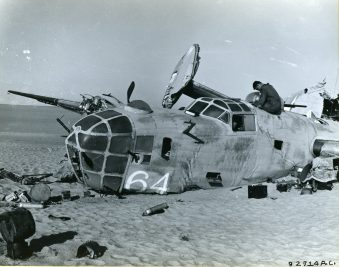 A top hatch is used for access to the B-24 by one of the members of the search party. The litter of gear around the aircraft is the result of sifting the interior for clues to the fate of the crew, missing for 16 years. Local ID: 342-B-ND-075-4-92714AC