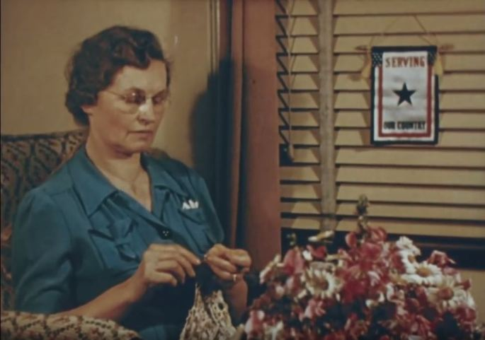 A woman knits by a window. There is a blue star banner attached to the window blinds, indicating that she has a child serving overseas.