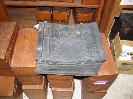 Original albums and wooden boxes used to house prints and negatives at the Norfolk Naval Shipyard.