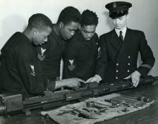 Under the direction of CGM Rex Ashley, three gunner's mates assemble and study a 20 mm gun, the type which they will man aboard the USS Mason. Trainees at Norfolk. Left to right: Albert A. Davis, Frank Wood, and Warren Vincent. (Local ID: 80-G-44826)