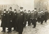 Policemen in Seattle, Washington wearing masks made by the Seattle Chapter of the Red Cross during the influenza epidemic. Local Identifier: 165-WW-269B-25