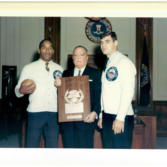 On December 4, 1967, Mr. O. J. Simpson, University of Southern California, Los Angeles, California, and Mr. Larry Csonka, Syracuse University, Syracuse, New York, members of The All American Football Coaches Association All-America Football Team, were photographed with FBI Director J. Edgar Hoover at FBI Headquarters, Washington, D.C., as Mr. Simpson presented Mr. Hoover an autographed football. Shown in Mr. Hoover's Office, left to right, are: Mr. Simpson, Mr. Hoover, and Mr. Csonka. (Local Identifier: 65-H-2838-01)