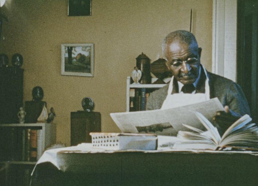 A seated George Washington Carver reads a newspaper.